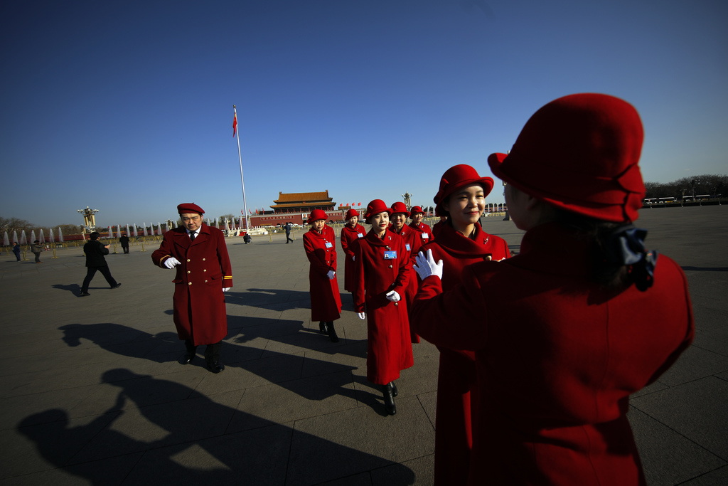In this Sunday, March 5, 2017 photo, a hospitality staffer poses her colleagues for photographs on Tiananmen Square during the National...