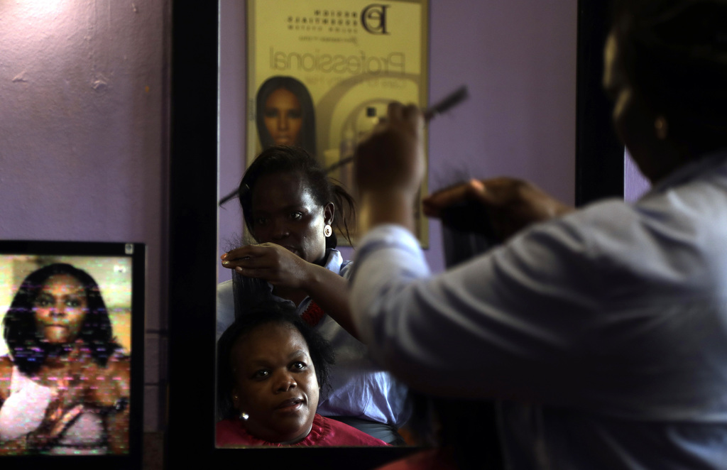 Thoko Mdlela, right, styles the hair of a client at her hair salon in Thokoza, south of Johannesburg, South Africa, Sunday, March 5, 20...