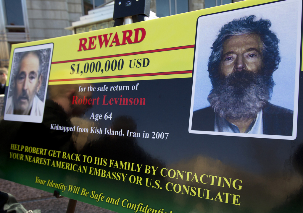 FILE- In this Tuesday, March 6, 2012 file photo, an FBI poster showing a composite image of former FBI agent Robert Levinson, right, of...
