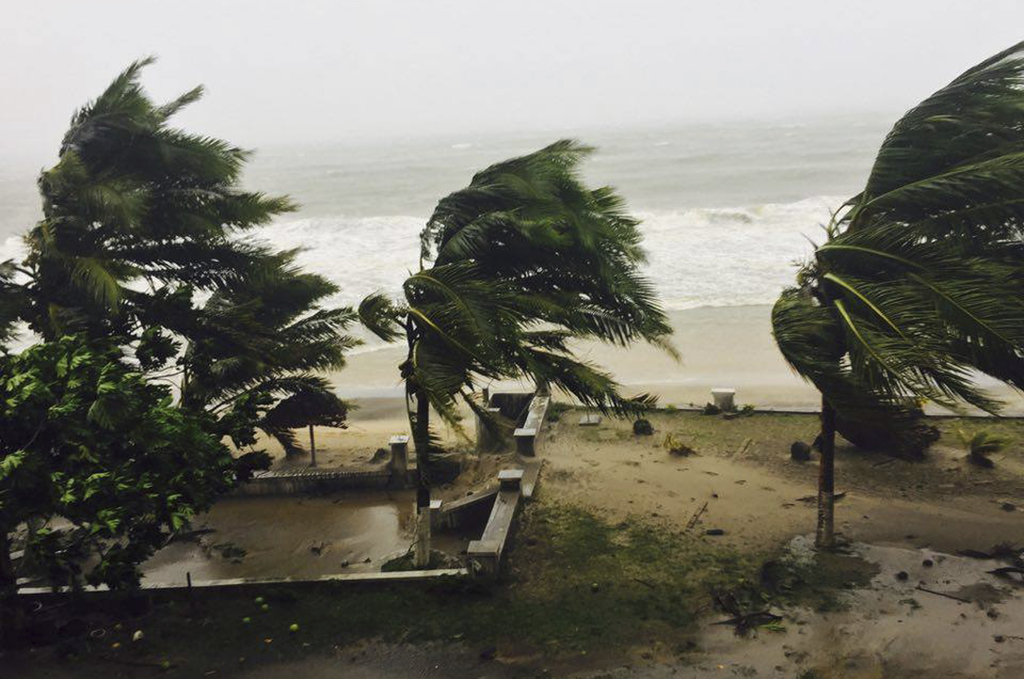 Trees are lashed by strong winds in Sambava, Madagascar Tuesday, March 7, 2017 as heavy rains and strong winds from a cyclone hit north...