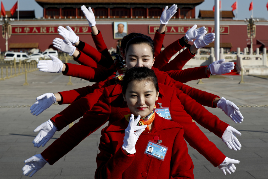 In this Sunday, March 5, 2017, photo, hospitality staff pose for photos on Tiananmen Square during the National People's Congress held ...