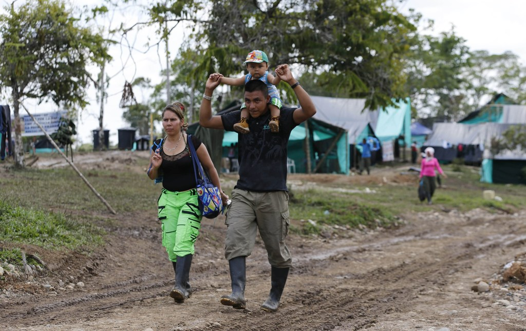 In this Tuesday, Feb. 28, 2017 photo, FARC rebel couple Jerly Suarez, left, and Vicente Pulecio walk to a cooking class with their 9-mo...
