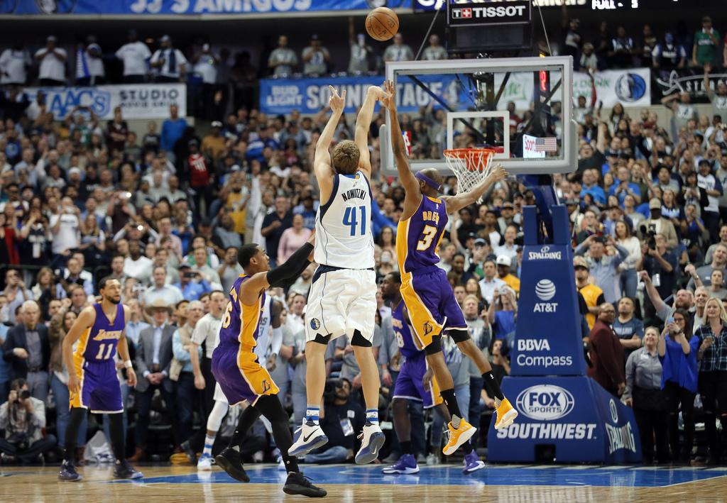 Dallas Mavericks' Dirk Nowitzki (41) of Germany shoots over Los Angeles Lakers' Jordan Clarkson (6) and Corey Brewer (3) sinking a thre...