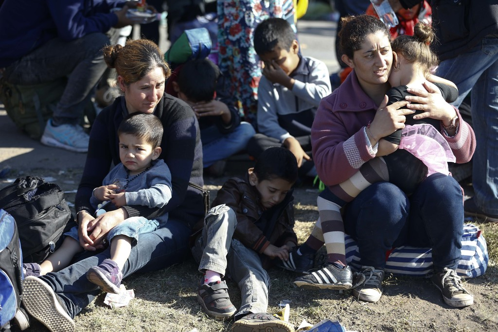 FILE - In this Sept. 9. 2015 file photo a group of migrants rest near the Hungarian border with Serbia, in Roszke, southern Hungary. A ...
