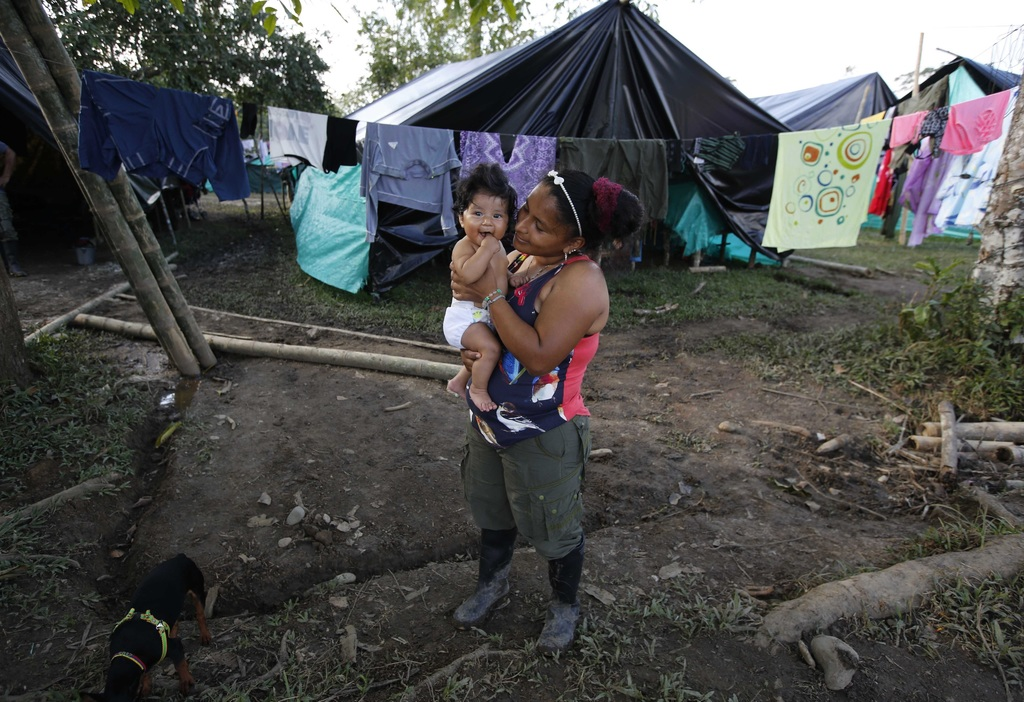 In this Tuesday, Feb. 28, 2017 photo, FARC rebel Sandra Saez holds her 4-month-old daughter Manuela outside her tent at a rebel camp in...
