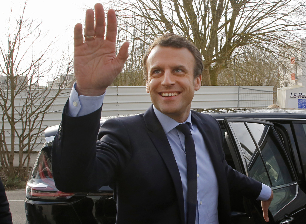 Independent centrist presidential candidate Emmanuel Macron waves to by standers as he arrives to visit the Moliere school in Les Murea...