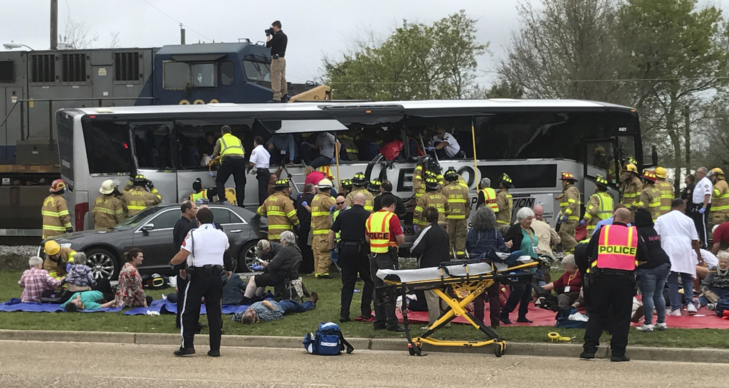 Biloxi, Miss., firefighters help passengers of a charter bus out of the damaged vehicle after the bus collided with a train Tuesday aft...