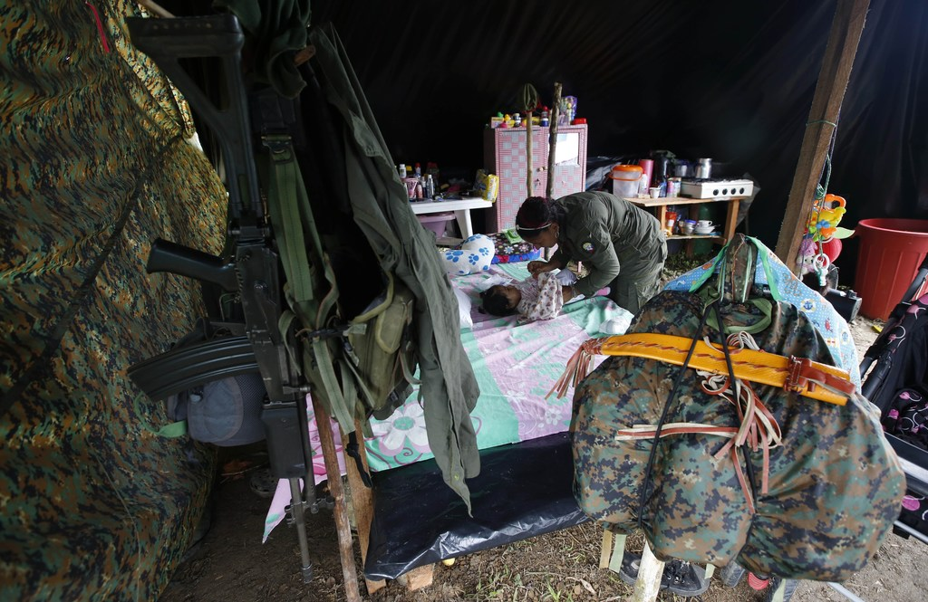 In this Tuesday, Feb. 28, 2017 photo, FARC rebel Sandra Saez changes her 4-month-old daughter Manuela inside her tent at a rebel camp i...