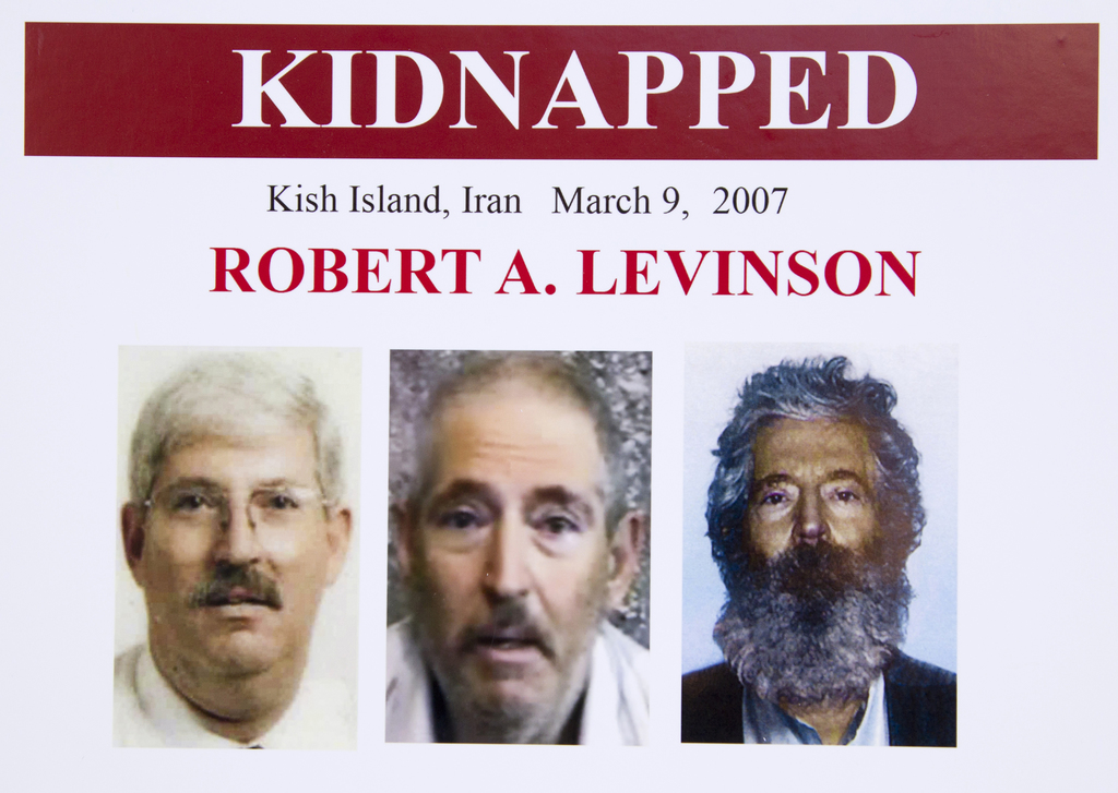 FILE- In this March 6, 2012 file photo, an FBI poster showing a composite image of former FBI agent Robert Levinson, right, of how he w...