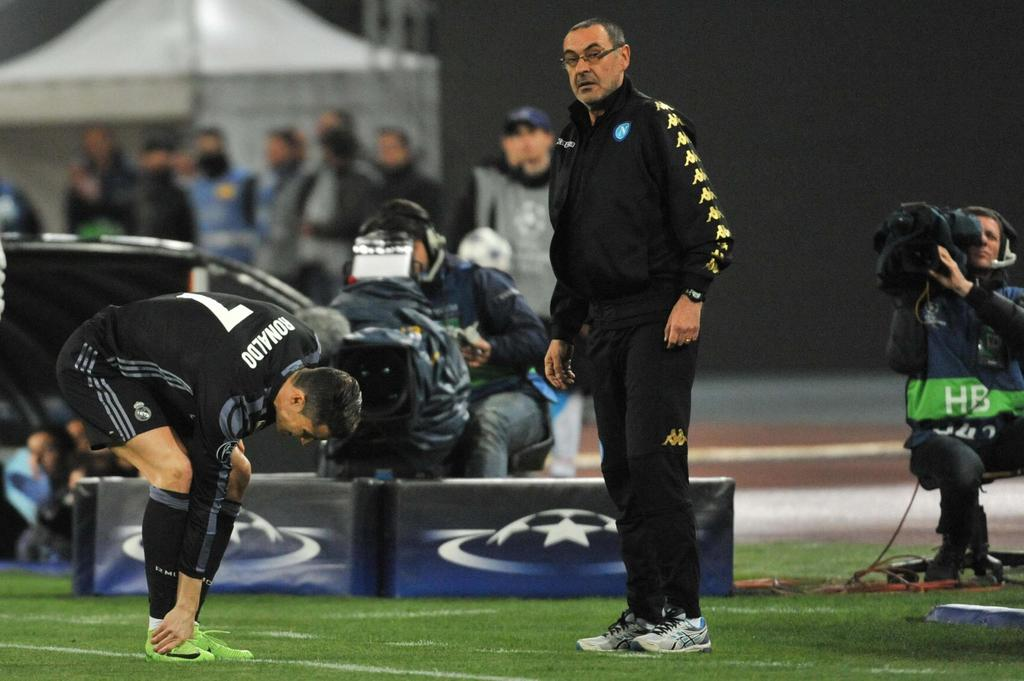 Napoli coach Maurizio Sarri, center, follows the game of a Champions League, round of 16, return-leg soccer match between Napoli and Re...
