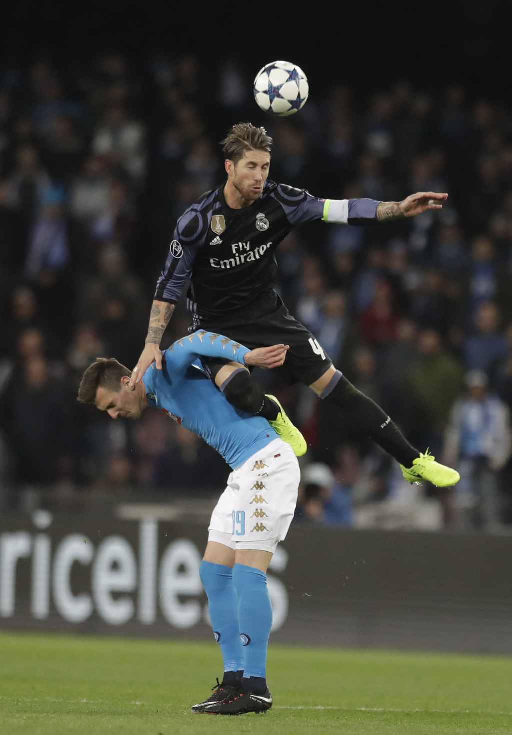 Real Madrid's Sergio Ramos jumps for the ball above Napoli's Nikola Maksimovic during the Champions League round of 16, second leg, soc...