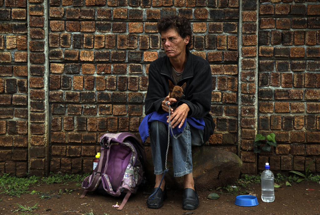 Raechel Van Der Burg, holds her dog as she sits on a street corner in Germiston, east of Johannesburg, South Africa, Friday, March 3, 2...