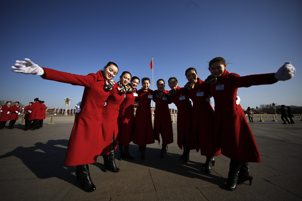 In this Sunday, March 5, 2017 photo, hospitality staff pose for photographs on Tiananmen Square during the National People's Congress h...