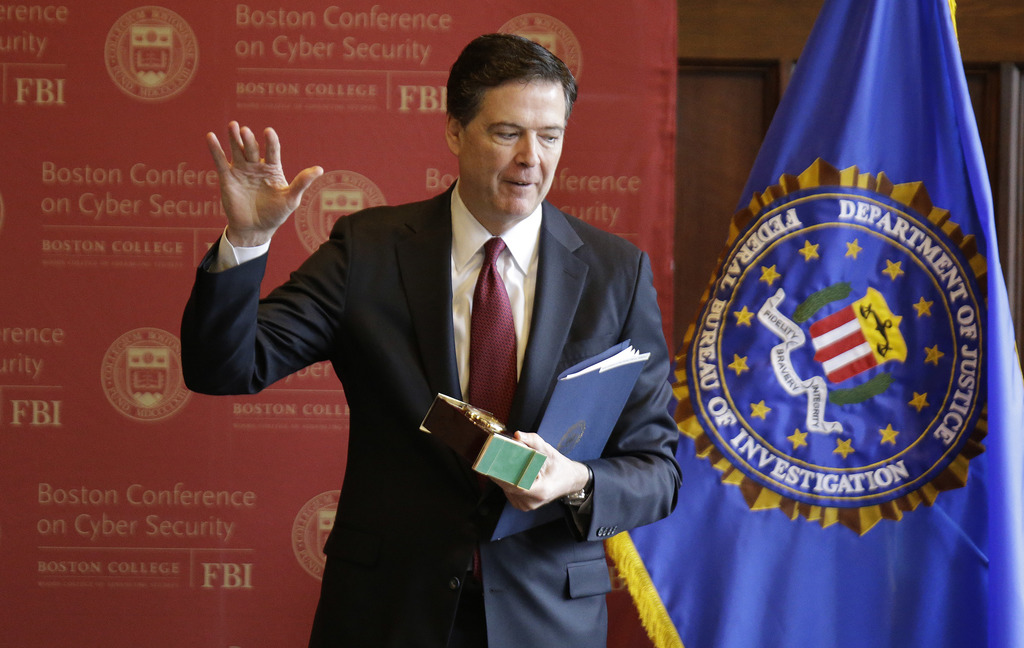FBI Director James Comey acknowledges applause as he leaves after speaking on cyber security at the first Boston Conference of Cyber Se...
