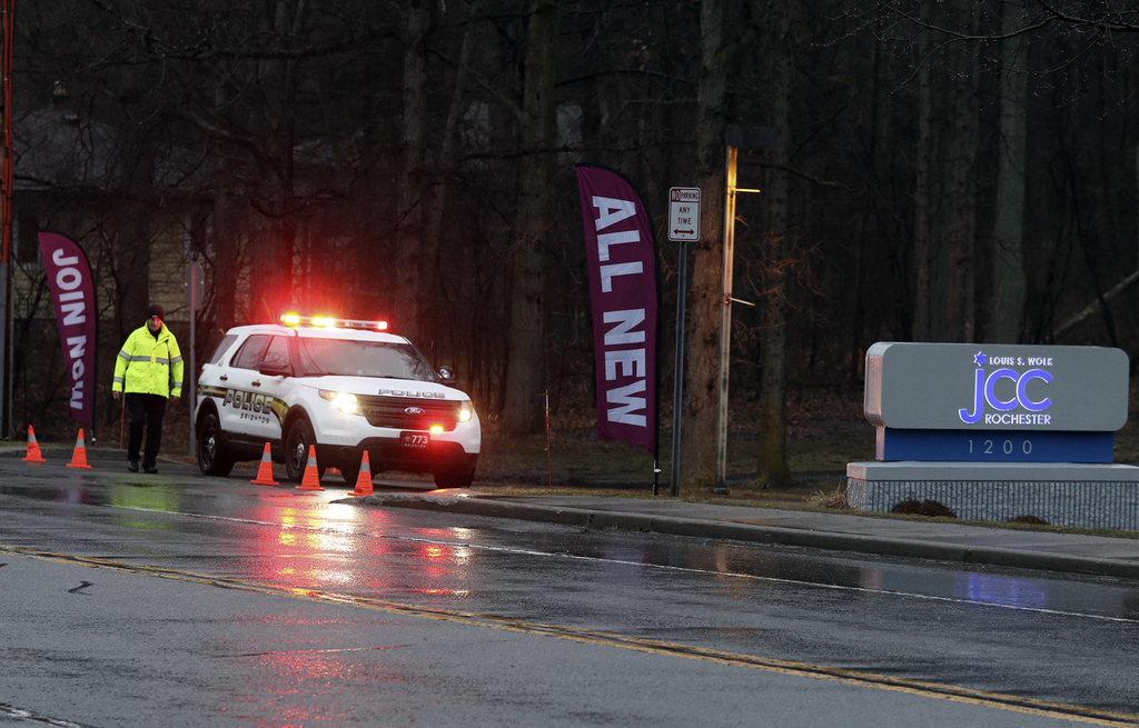 A police officer stands in front of the Louis S. Wolk Jewish Community Center of Greater Rochester after a bomb threat was reported in ...