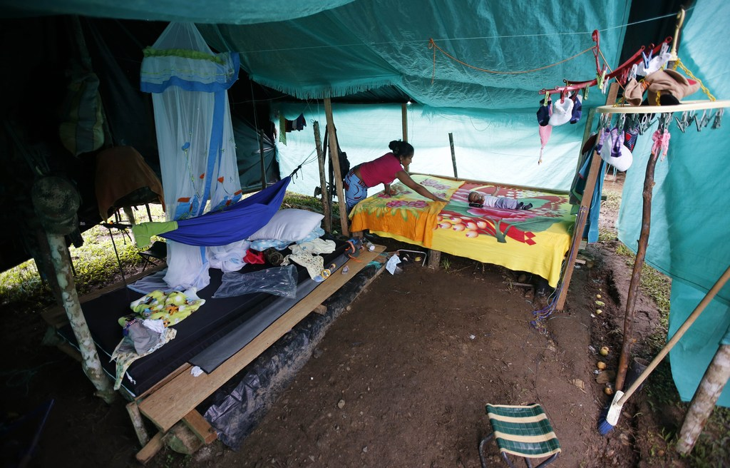 In this Tuesday, Feb. 28, 2017 photo, FARC rebel Deisy Garcia makes her bed where her 3-month-old son Junior Alexis rests inside their ...