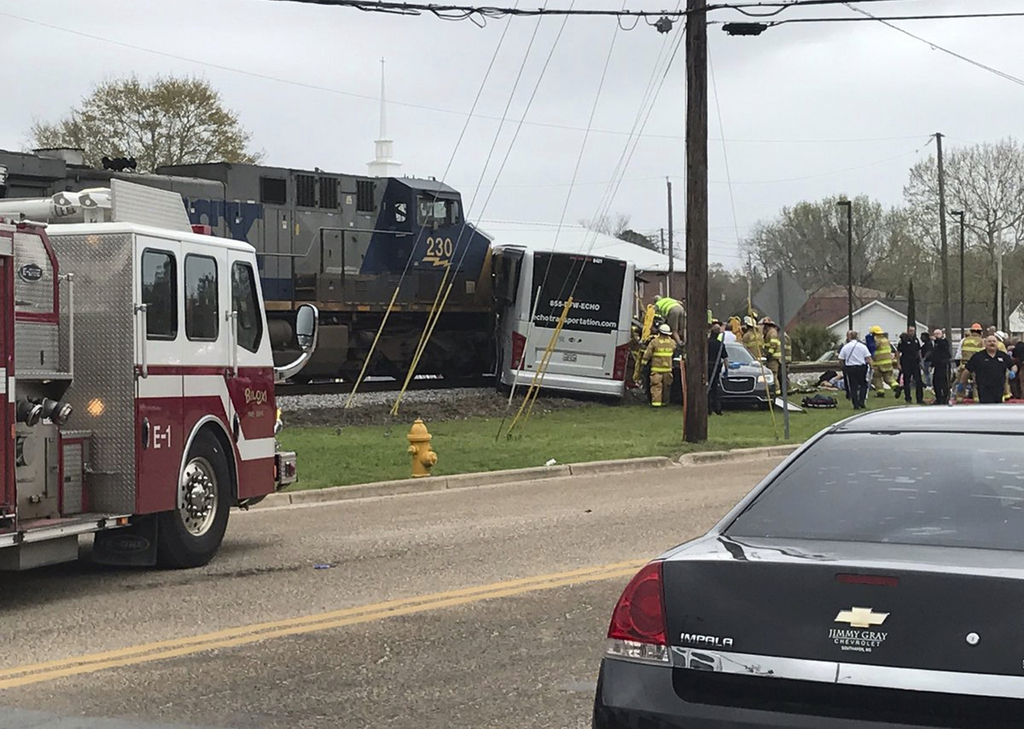In this photo made from video and released by WLOX-TV, Authorities pull passengers off a bus after colliding with CSX freight train, Tu...