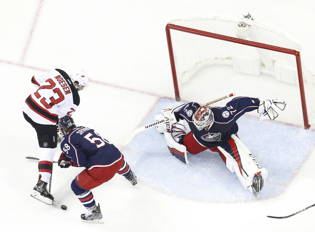 Columbus Blue Jackets' Sergei Bobrovsky, right, of Russia, makes a save as teammate David Savard, center, and New Jersey Devils' Stefan...