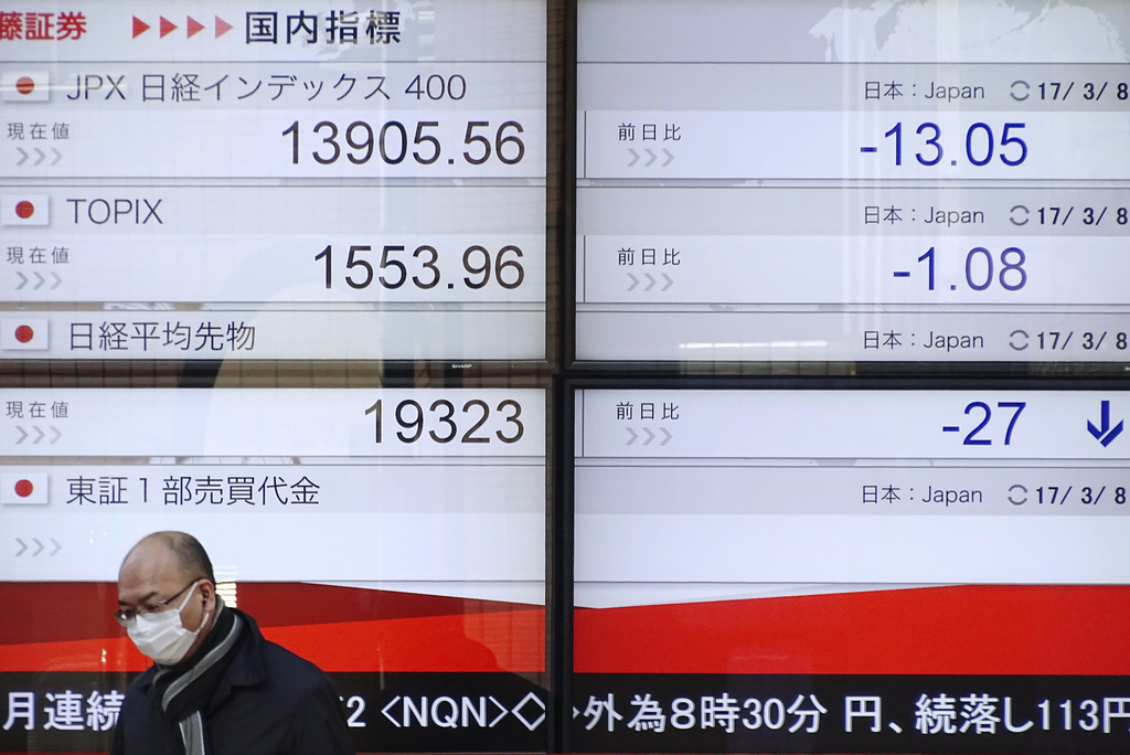A man walks by an electronic stock board of securities firms in Tokyo, Wednesday, March 8, 2017. Asian stocks declined Wednesday after ...