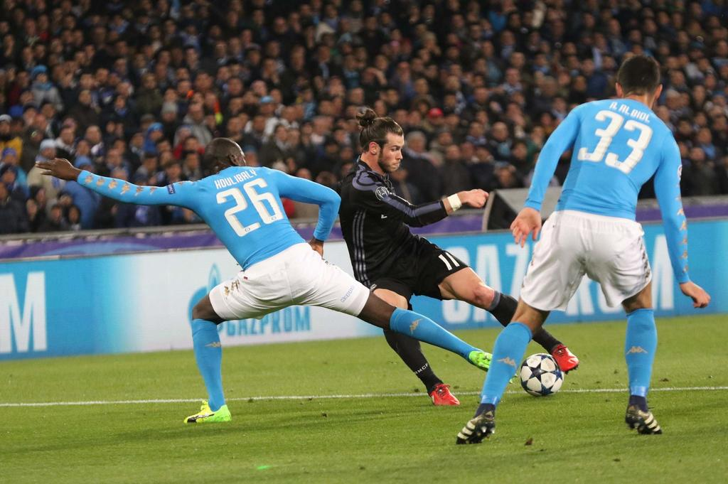 Real Madrid's Gareth Bale, center, dribbles past Napoli's Kalidou Coulibaly, left, and Napoli's Raul Albiol during a Champions League, ...