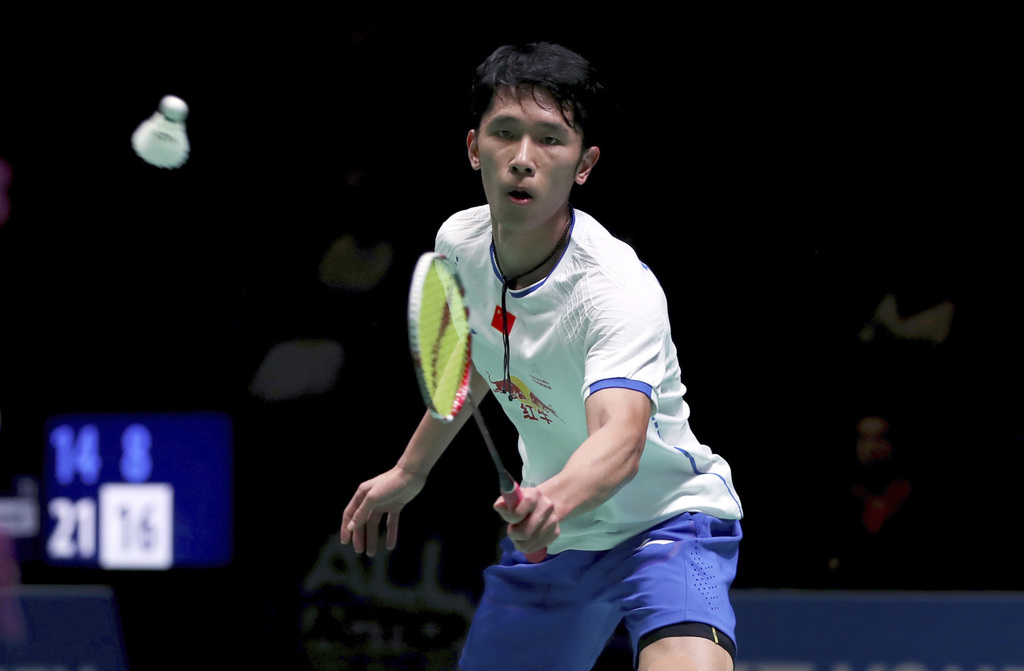 China's Tian Houwei in action against Indonesia's Tommy Sugiarto during round one of the men's singles on day two of the All England Op...
