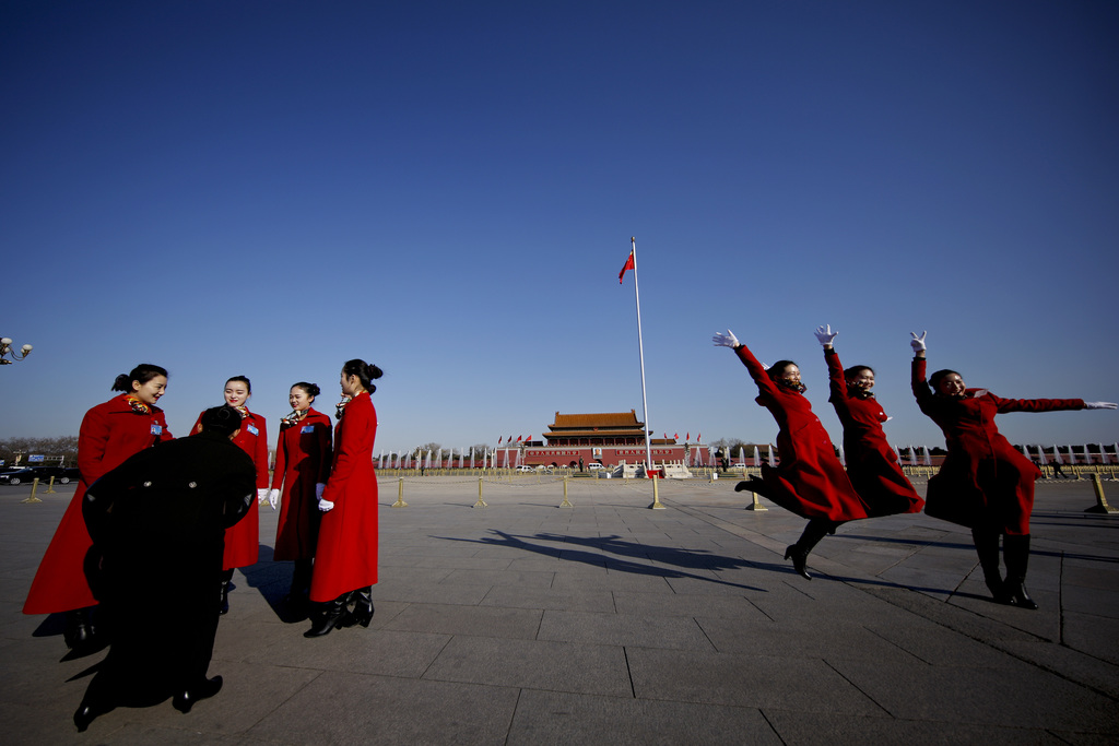 In this Sunday, March 5, 2017 photo, hospitality staff jump as they pose for photographs on Tiananmen Square during the National People...