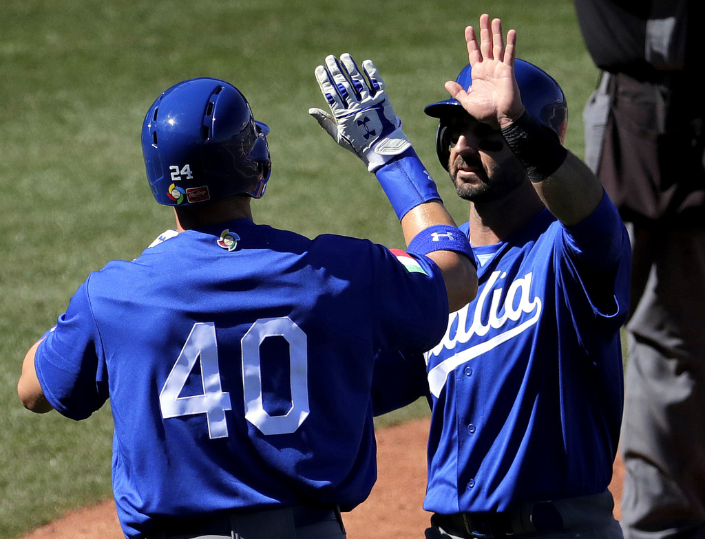 Italy's Brandon Nimmo and Daniel Descalso high five after scoring on a base hit by teammate Francisco Cervelli against the Chicago Cubs...
