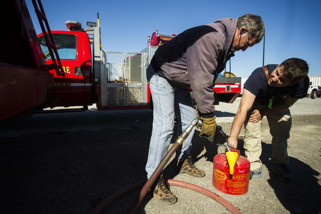 Brad Thompson, owner of Bridgman Oil, left, assists Colwich firefighter Mike Rau, right, in filling a fire truck with gasoline at the H...