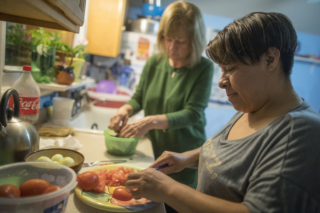 In this Tuesday, Feb. 28, 2017 photo, Ruth Silverberg, left, helps Maribel Torres prepare dinner at Maribel's home in the Staten Island...