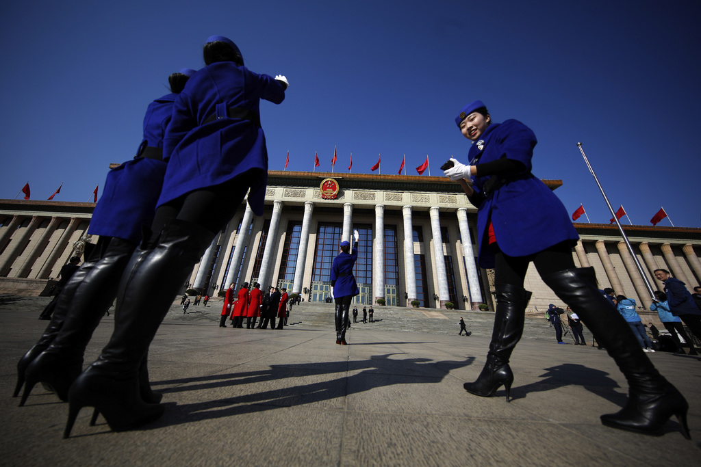In this Sunday, March 5, 2017, photo, hospitality staff take souvenir photos in front of the Great Hall of the People where the Nationa...