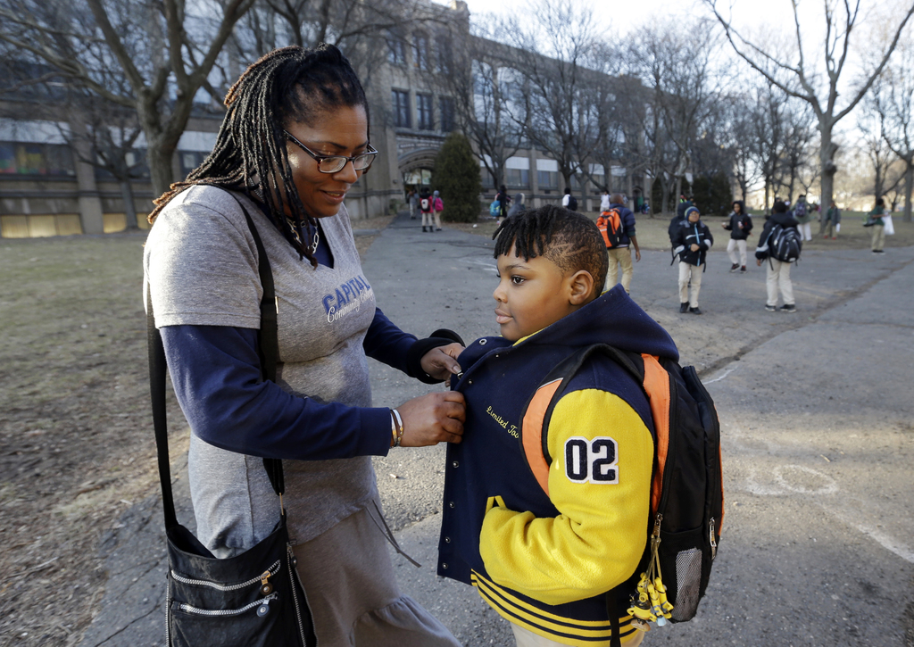 In this Feb. 23, 2017 photo, Natalie Langlaise snaps the jacket of her son Justin outside the Martin Luther King Jr. Elementary School ...