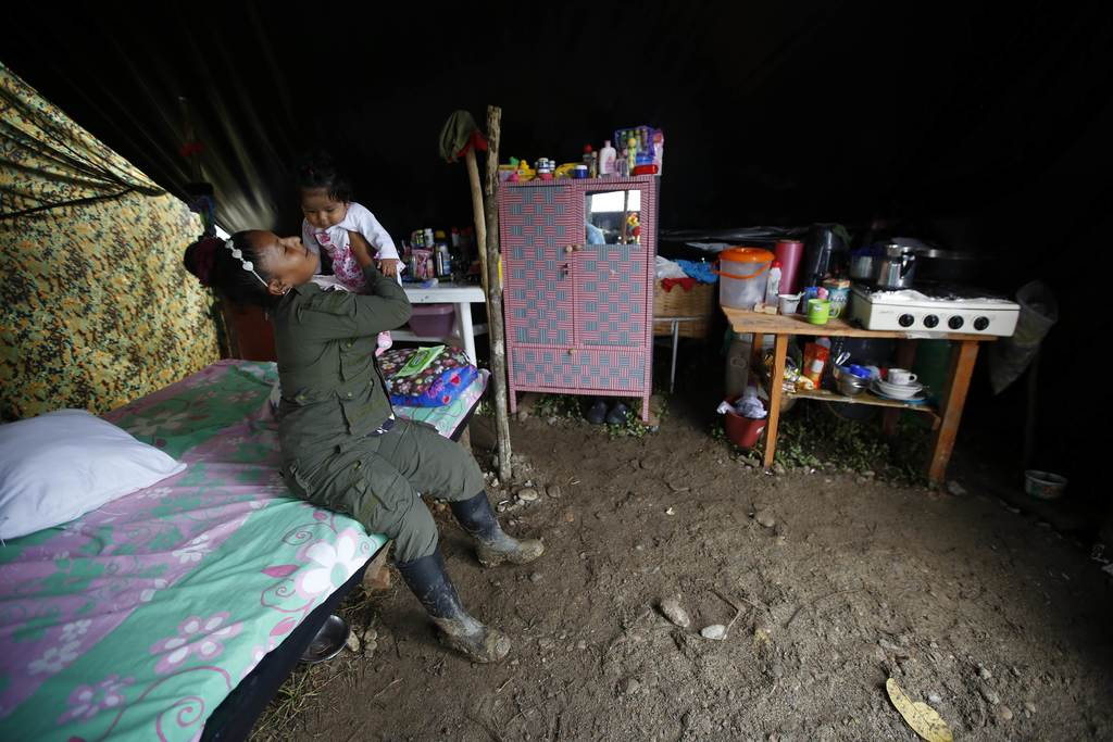 In this Tuesday, Feb. 28, 2017 photo, FARC rebel Sandra Saez plays with her 4-month-old daughter Manuela inside their tent at a rebel c...