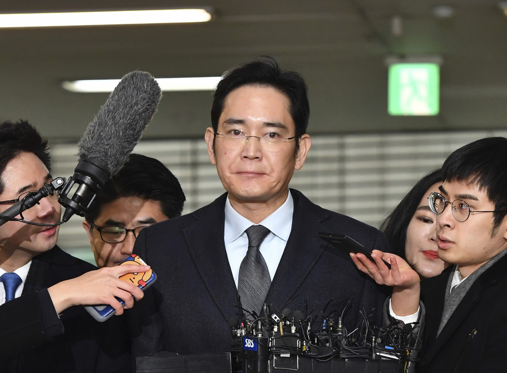 FILE - In this Feb. 13, 2017 file photo, Lee Jae-yong, center, vice chairman of Samsung Electronics, arrives to be questioned as a susp...