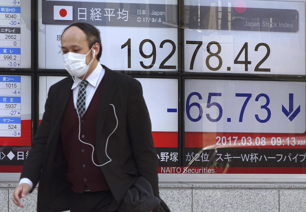 A man walks by an electronic stock board of a securities firm in Tokyo, Wednesday, March 8, 2017. Asian stocks declined Wednesday after...