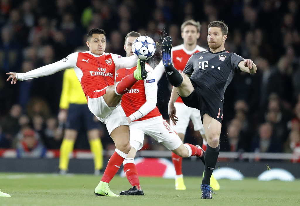 Arsenal's Alexis Sanchez, left, and Bayern's Xabi Alonso battle for the ball during the Champions League round of 16 second leg soccer ...