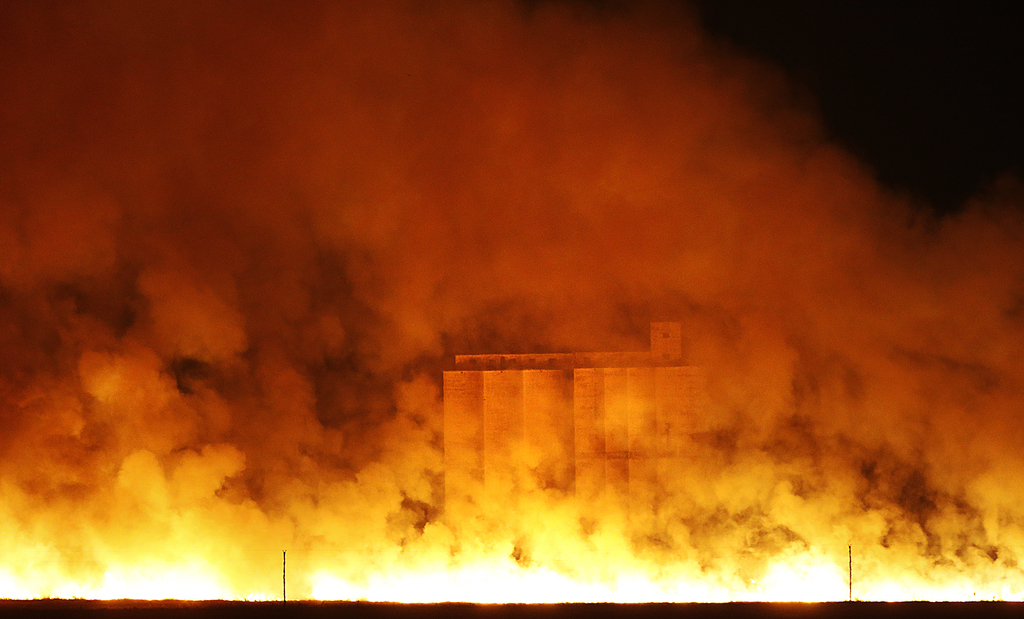 Flames and smoke envelope a grain elevator in Sitka, Kan., early Tuesday, March 7, 2017. Grass fires fanned by gusting winds scorched s...