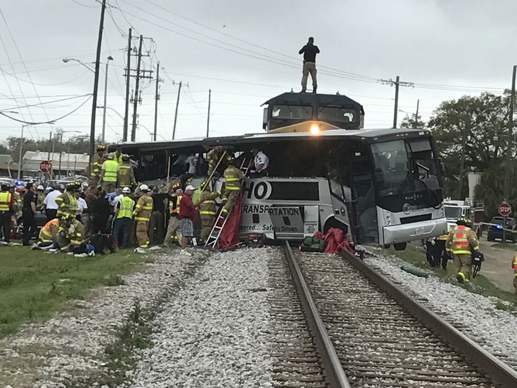 Biloxi firefighters assist injured passengers after their charter bus collided with a train in Biloxi, Miss., Tuesday, March 7, 2017.  ...