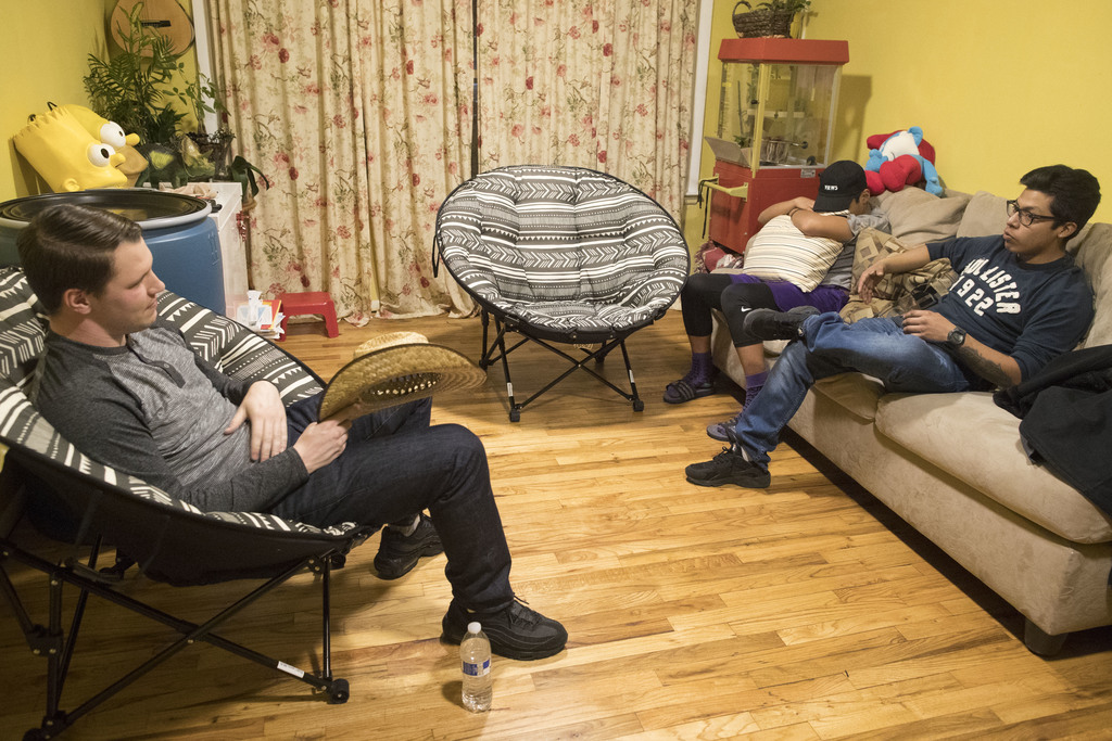 In this Tuesday, Feb. 28, 2017 photo, Jesse Silverberg, left, talks to Axel, right, and Jose Juarez before dinner at Maribel Torres hom...