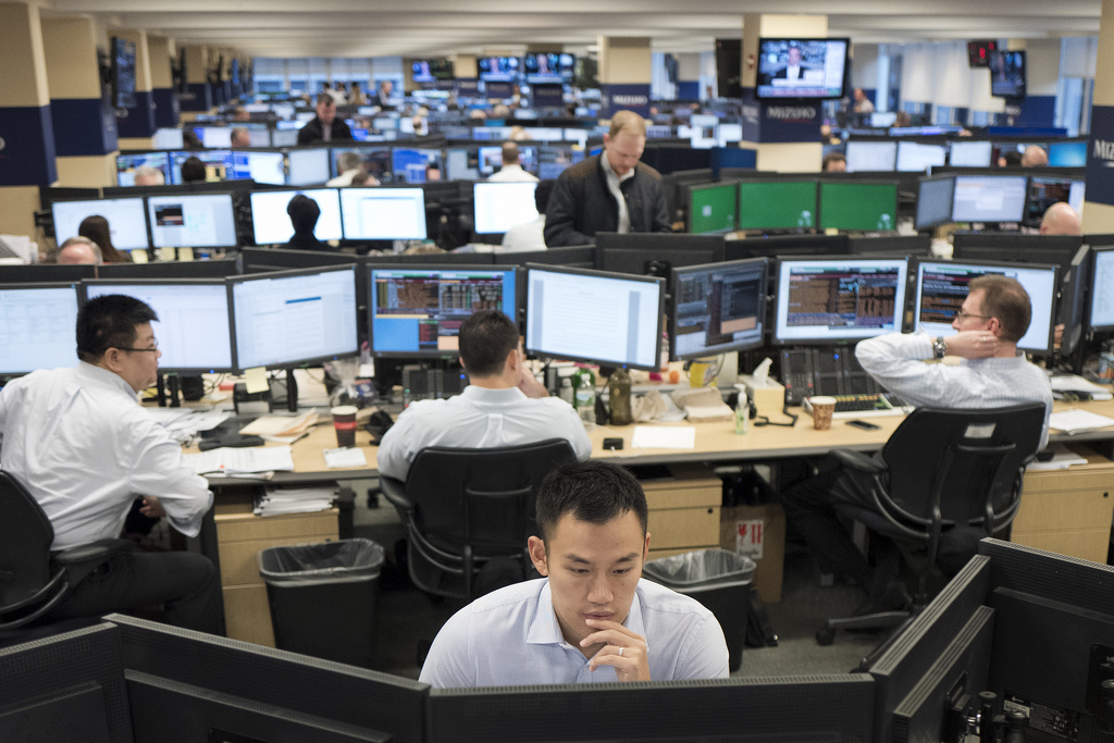 In this Jan. 12, 2017, photo, traders work on the Mizuho Americas trading floor in New York. Global stock markets traded on a soft note...