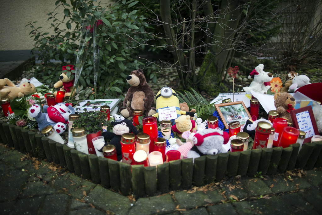 Soft toys, candles and flowers are placed in front of a house in Herne, Germany, Wednesday, March 8, 2017, where the body of a nine-yea...
