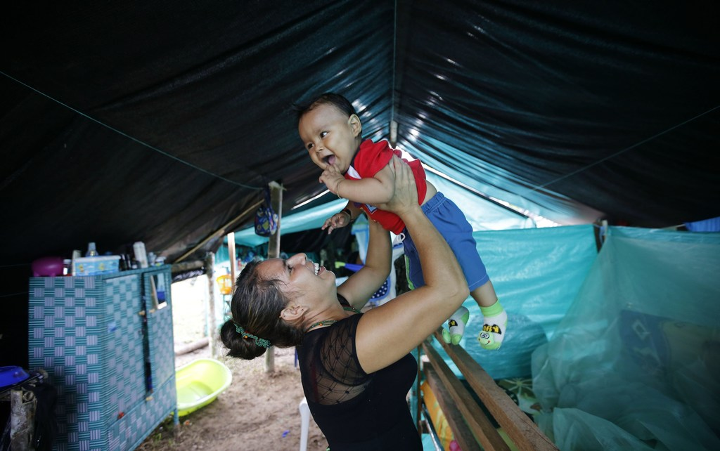 In this Tuesday, Feb. 28, 2017 photo, FARC rebel Jerly Suarez holds up her 9-month-old son Dainer inside her tent at a rebel camp in a ...