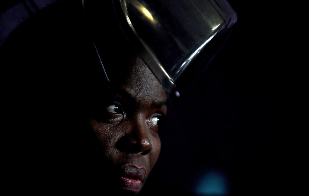 Thoko Mdlela sits under a hair dryer at her hair salon in Thokoza, south of Johannesburg, South Africa, Wednesday, March 8, 2017. 41-ye...