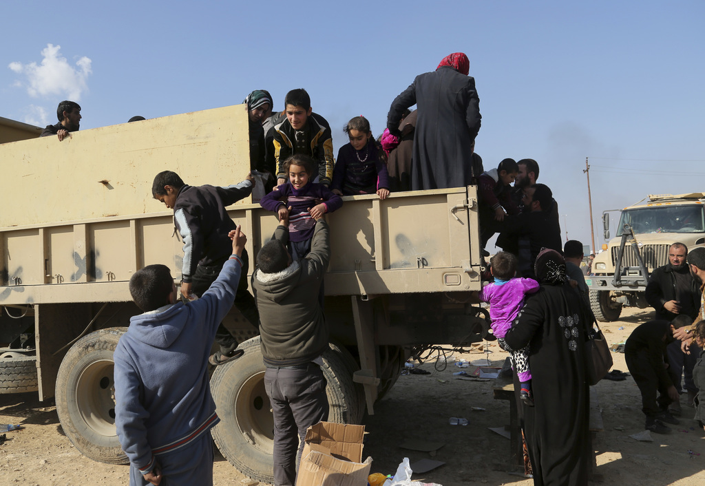 Iraqi security forces help transfer displaced Iraqi civilians who fled their homes during fighting in Mosul between Iraqi special force...