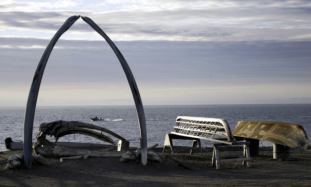 FILE - In this Aug. 12, 2005, file photo, a boat drives past a skin boat display near whale bones and an arch made of a whale jaw on th...
