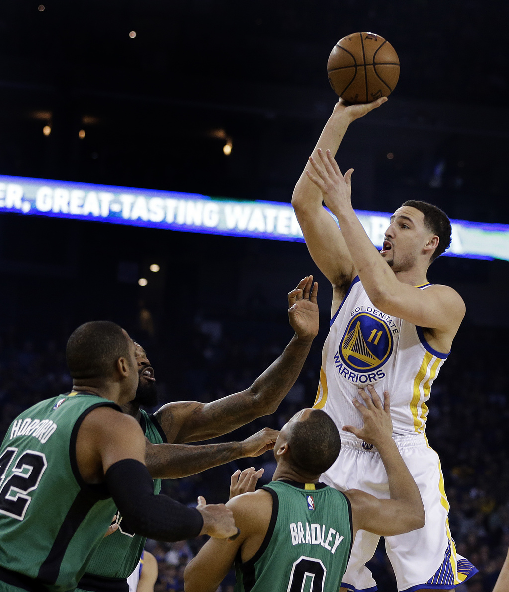 Golden State Warriors' Klay Thompson, right, shoots over Boston Celtics' Al Horford, left, and Avery Bradley (0) during the first half ...