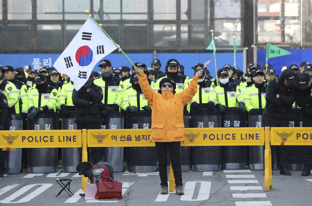 A supporter of impeached South Korean President Park Geun-hye holds a national flag as police officers stand guard near the Constitutio...