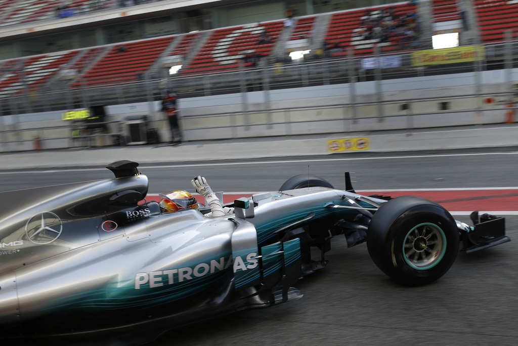 Mercedes driver Lewis Hamilton of Britain waves his hands to supporters as he leaves the team box during a Formula One pre-season testi...