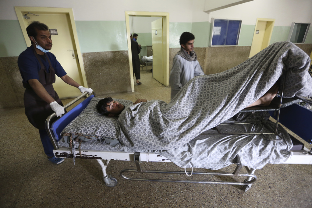 Afghan health workers carry a wounded Afghan at a hospital after the Wednesday's attack and shooting at a military hospital in Kabul, A...