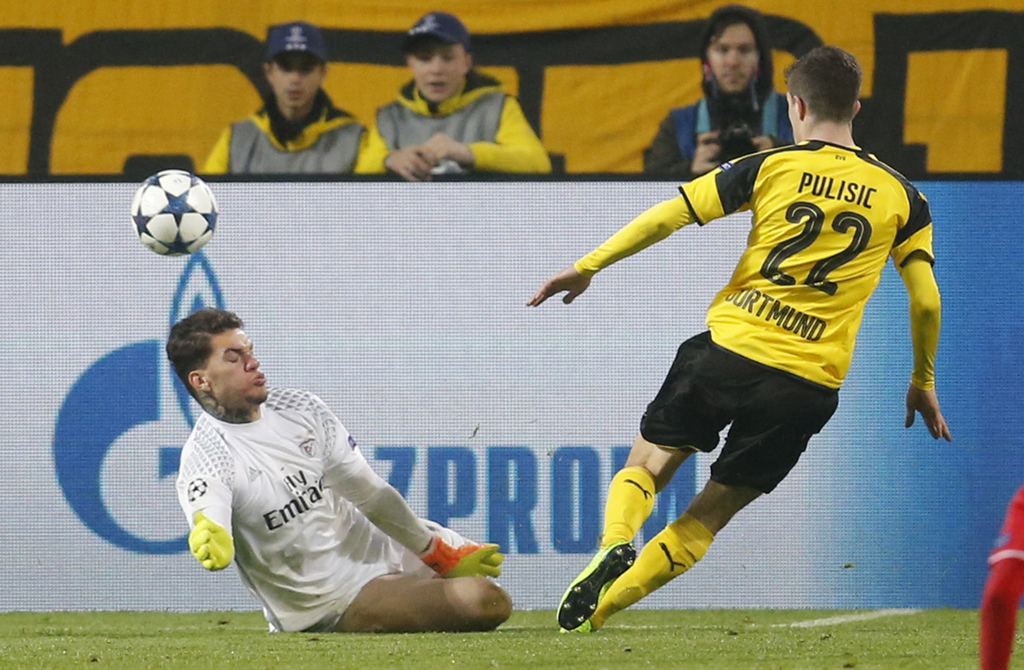 Dortmund's Christian Pulisic, right, scores his side's second goal past Benfica goalkeeper Ederson during the Champions League round of...