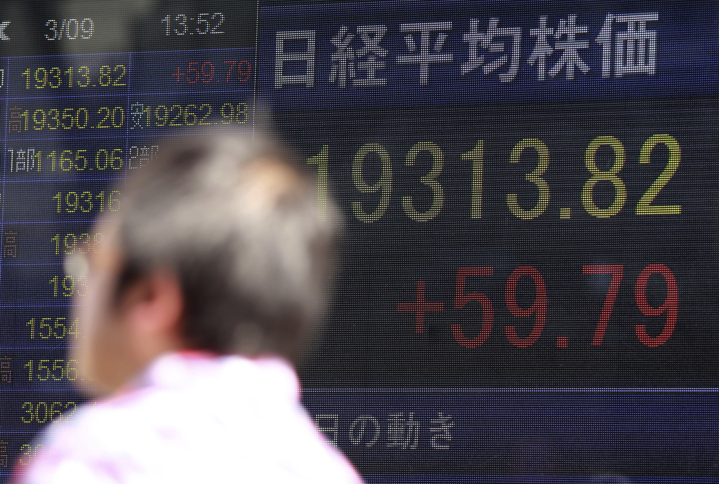 A man walks by an electronic stock board of a securities firm in Tokyo, Thursday, March 9, 2017. Asian stock markets were mostly lower ...
